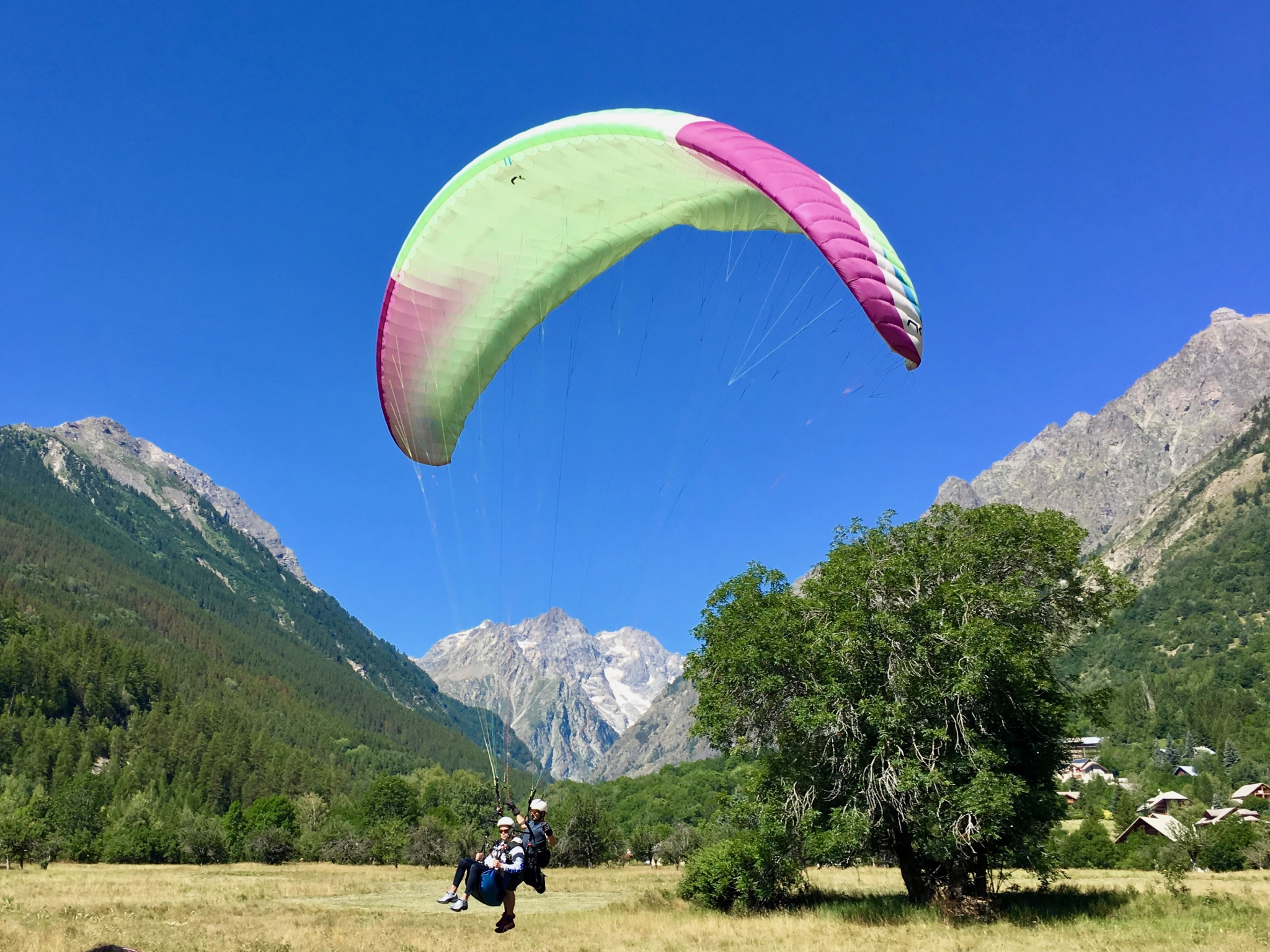 Tandem paraglider landing in field next to Alpbase